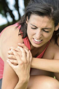 Young woman grabbing her shoulder with an expression of pain because of an muscle injury.